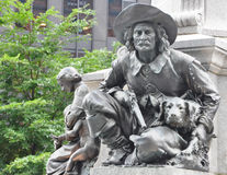 Statue of frontier man. Crouched with gun and dog outdoors Royalty Free Stock Photography