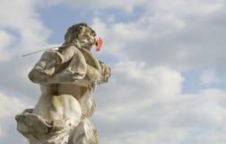Statue géante en pierre avec l'enfant en bas âge et la fleur rouge Image libre de droits