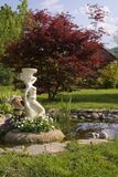 Statue in garden pond Stock Photos