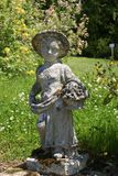 Statue of a girl carrying a basket of flowers in a garden Stock Images
