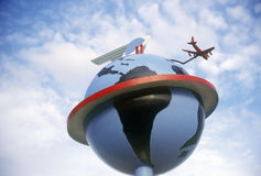Statue of globe with airplane circling it, CA Royalty Free Stock Photos