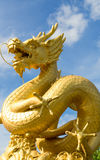 Statue of golden dragon with blue sky Royalty Free Stock Photos