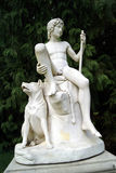 Statue of a shepherd boy and his dog. Garden decoration of a Roman statue on a plinth. 1817 Marble statue by Bertel Thorvaldsen of a nude shepherd boy sitting on Stock Photo