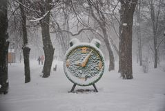 Time froze under the snow. A statue of green clock stands in a snowy park. Time froze under the snow stock image