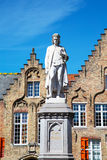 Statue of Hans Memling and medieval house exterior against blue sky in Brugge, Belguim Royalty Free Stock Images