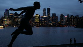 Statue of Harry Jerome with downtown skyline in the background, Stanley Park, Vancouver,. British Columbia, Canada. Henry `Harry` Winston Jerome was a famous stock video footage