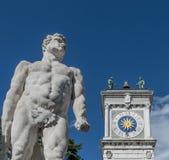 The statue of Hercules with the clock tower of the San Giovanni colonnade, Piazza della Libertà, Udine, Friuli, Italy. Europe stock photo