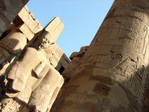 Statue & hieroglyph. Ancient statue of a pharao and a pillar with hieroglyphs in Luxor Royalty Free Stock Photography