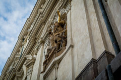 Statue holding a golden cross on the side of a building in Prague Royalty Free Stock Image