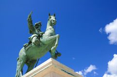 Statue of a man riding a horse against blue sky  Royalty Free Stock Image