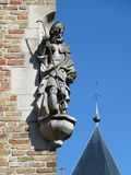 Statue at a house end face. Sculpture of the wanderer, Brugge Royalty Free Stock Photography