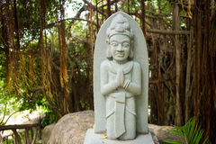 Statue of indhuism and buddhism prayer near banyan tree Royalty Free Stock Image