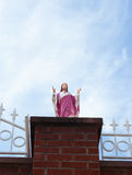 Statue of Jesus with blue sky background. Statue of Jesus on a brick column with blue sky on the back Stock Image