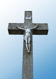 Statue of Jesus on a stone cross. And blue background Stock Photo