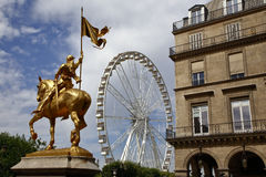 A statue of Joan of Arc stands in the Place des Victoires with a large ferris wheel in the Tuileries Gardens, Paris France - shot  Royalty Free Stock Photo