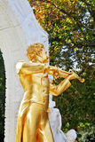The  statue of Johann Strauss, playing the violin. Park in Vienna.  Elegant gilded statue of Johann Strauss, playing the violin in white marble arch Stock Photo