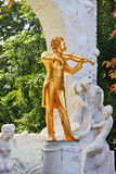 The statue of Johann Strauss with violin. Waltz King plays. Gorgeous gilded statue of Johann Strauss with violin in Vienna park Stock Photography