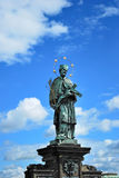Statue of John of Nepomuk in Prague on the Charles Bridge on the background of blue sky with clouds. Royalty Free Stock Images