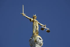 Statue of justice. A woman holding a sword in her right hand standing for the power to punish and a balance in her left hand standing for equity on the roof of Stock Photography