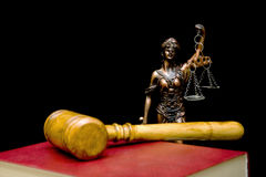 Statue of justice on a black background. Gavel and law book in the foreground out of focus. Horizontal photo stock photo