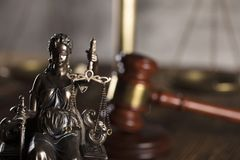 Law and justice theme. Place for text. Statue of justice and  gavel of the judge on a stone background and rustic wooden table Stock Photography