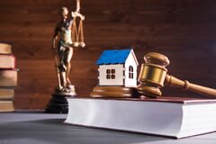 statue of justice, house and hammer