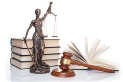 Statue of justice, judge`s hammer behind books on a white background.  stock images