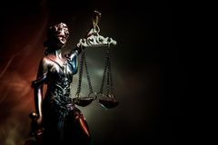 The Statue of Justice - lady justice or Iustitia / Justitia the Roman goddess of Justice on a dark fire background. Selective focus royalty free stock photography