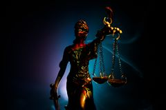 The Statue of Justice - lady justice or Iustitia / Justitia the Roman goddess of Justice on a dark fire background. Selective focus stock photos