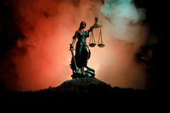 The Statue of Justice - lady justice or Iustitia / Justitia the Roman goddess of Justice on a dark fire background. Selective focus royalty free stock image