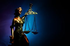 The Statue of Justice - lady justice or Iustitia / Justitia the Roman goddess of Justice on a dark fire background. Selective focus stock photo