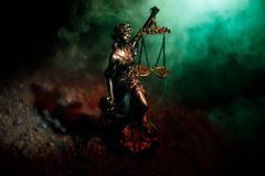 The Statue of Justice - lady justice or Iustitia / Justitia the Roman goddess of Justice on a dark fire background. Selective focus stock image