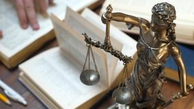 Lawyer Working with Ppapers and Law Books in Courtroom or Office