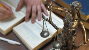 The Statue of Justice. Lawyer working with papers and law books in courtroom or office. Concept of justice and law, attorney or court judge stock video