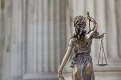 The statue of justice Themis or Iustitia, the blindfolded goddess of justice against an ionic order colonnade, as a legal concept. The statue of justice Themis royalty free stock photo