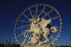 Statue of King of Fame riding Pegasus on the Place de la Concorde with ferris wheel at background, Paris, France Royalty Free Stock Photography