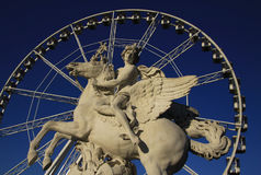 Statue of King of Fame riding Pegasus on the Place de la Concorde with ferris wheel at background, Paris, France Stock Photos