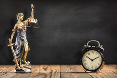 Statue of Lady Justice with Alarm Clock on Black Board stock photos