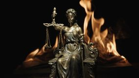 Statue of Lady Justice on the background of the flame of a burning book stock image