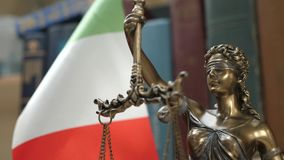 Statue of Lady Justice with Bookshelf with Books and Italy Flag Background. Tribunal and justice concept. Consultation with insurance lawyer and customer stock video