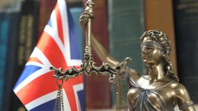 Statue of Lady Justice with Bookshelf with Books and UK Flag Background. Statue of Lady Justice with Bookshelf with Books and United Kingdom Flag Background stock video footage