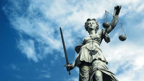 Statue Of Lady Justice With Clouds Passing