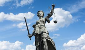 Statue of Lady Justice Justitia in Frankfurt, Germany. The Statue of Justice - lady justice or Iustitia / Justitia the Roman goddess of Justice against blue royalty free stock photos