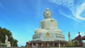 A statue of a large white Buddha. religious asian shrine. temple on the mountain. Buddhism, travel and tourism. A statue of a large white Buddha. religious stock video footage