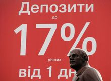 Statue of Lenin in Front of Bank Advertisement Stock Image