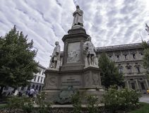 Statue of Leonardo da Vinci with a checkered sky, Milan, Italy. Statue of Leonardo da Vinci with a checkered sky in front of the famous Opera of Milan, Italy stock photo