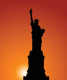 Statue of Liberty. Vector silhouette of a Statue of Freedom on a background of the evening sky Stock Photos