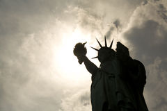 Statue of liberty. Silhouette over a bright spot in the sky Stock Photos