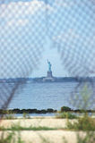 Statue of Liberty. Liberty at Risk close-up of a ripped fence with Statue of Liberty in the distance Royalty Free Stock Image