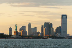 The Statue of Liberty against New Jersey skyline on sunset stock photo